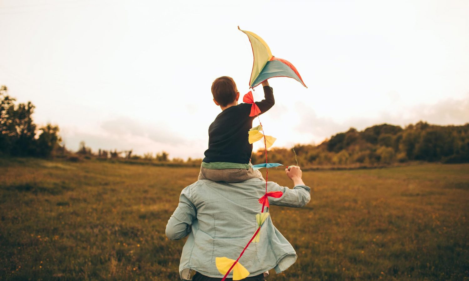 A child with a kite on his father's shoulders