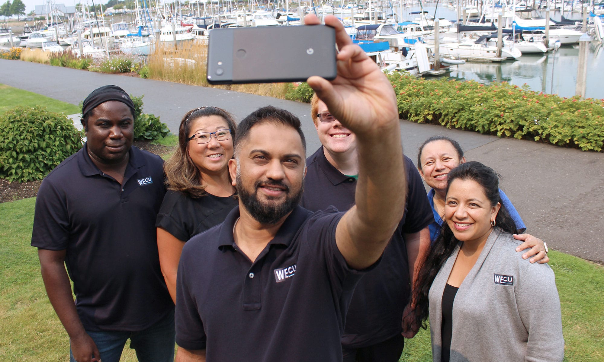 WECU volunteers smiling for a selfie.