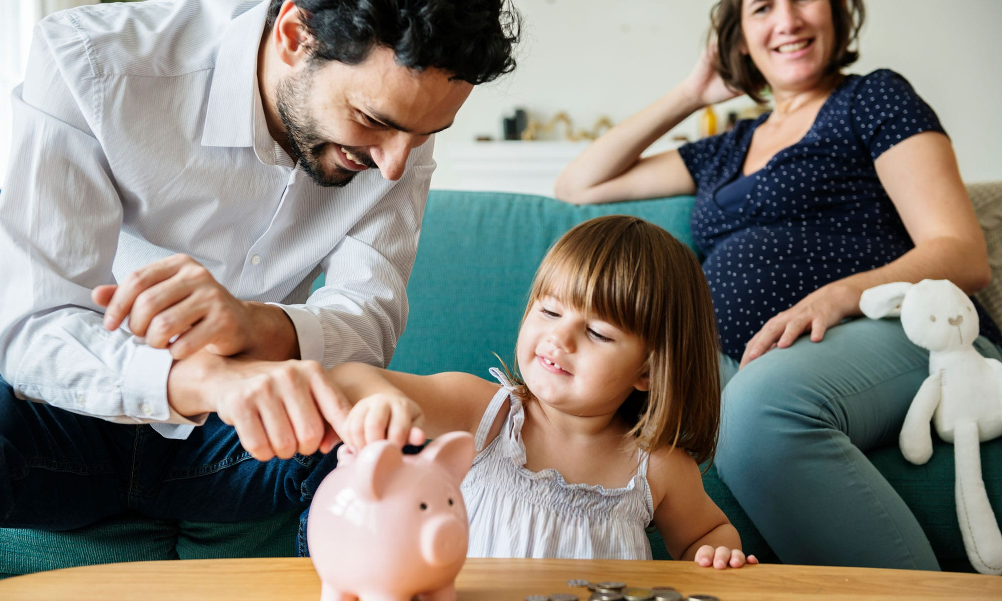 Father shows his daughter how to save money with a piggy bank.