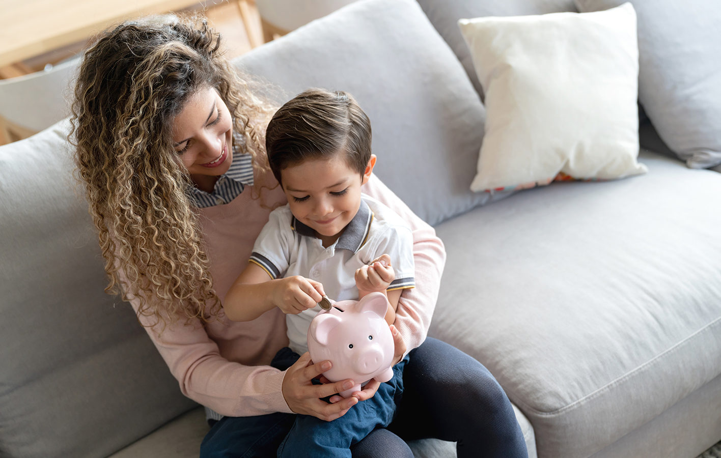 A mother showing her kid how to save money with a piggy bank
