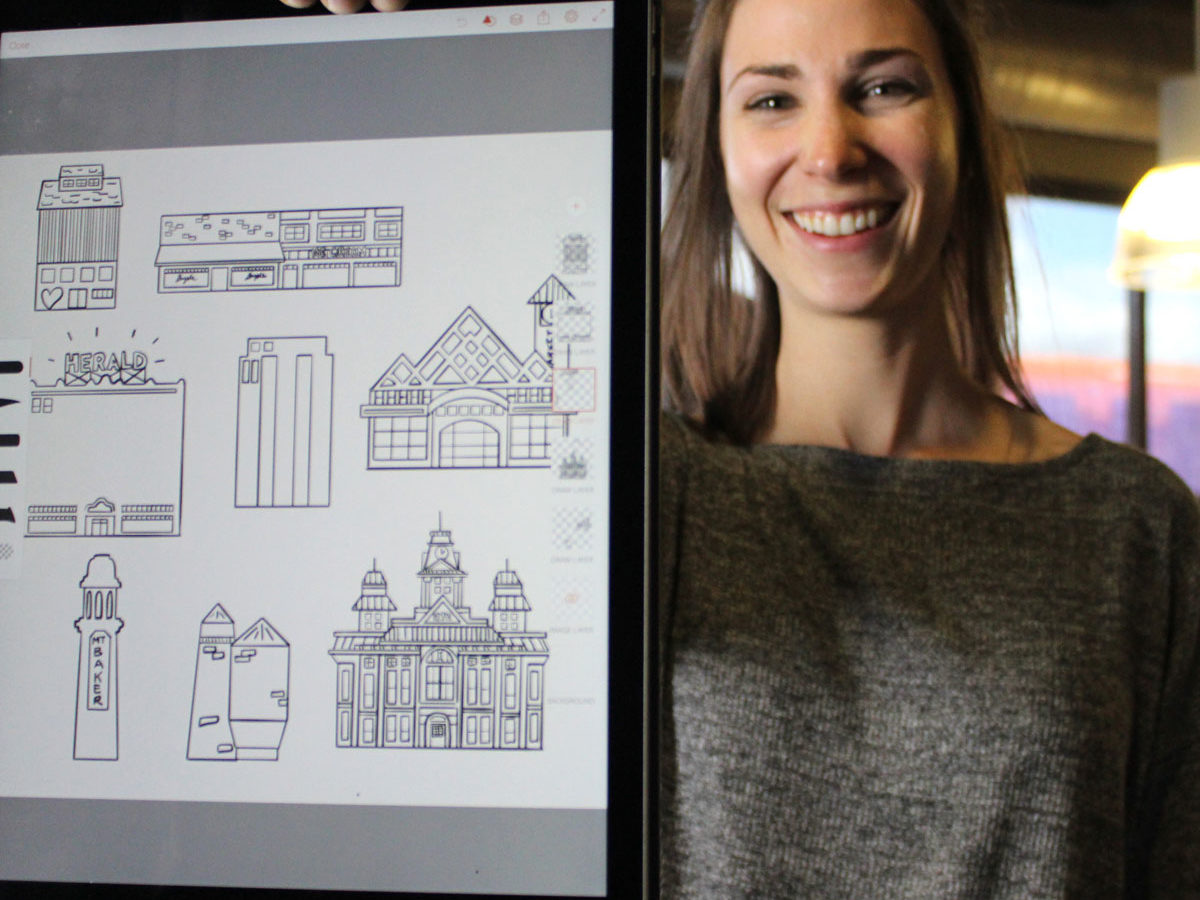 Brinn - a local graphic designer, holding some of her graphics up