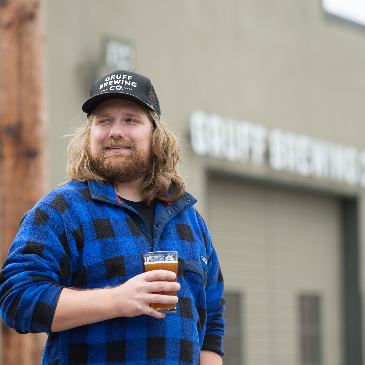 An employee from Gruff poses with beer in hand and a Gruff Brewing Co. cap.