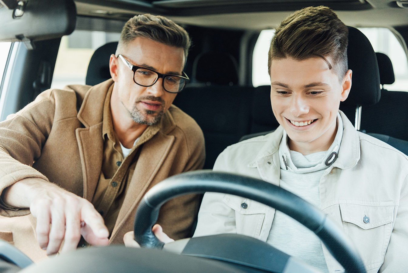Man showing his child how to drive a car
