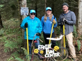 "Team WECU volunteers pose next to a bike with ""Family fun center"" posted on it"