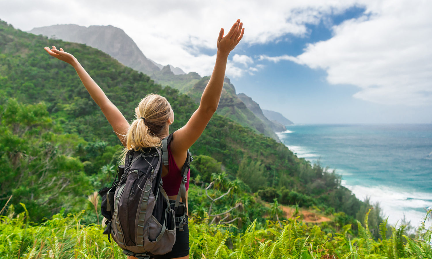 Woman raising her hands to the sky while on a hike