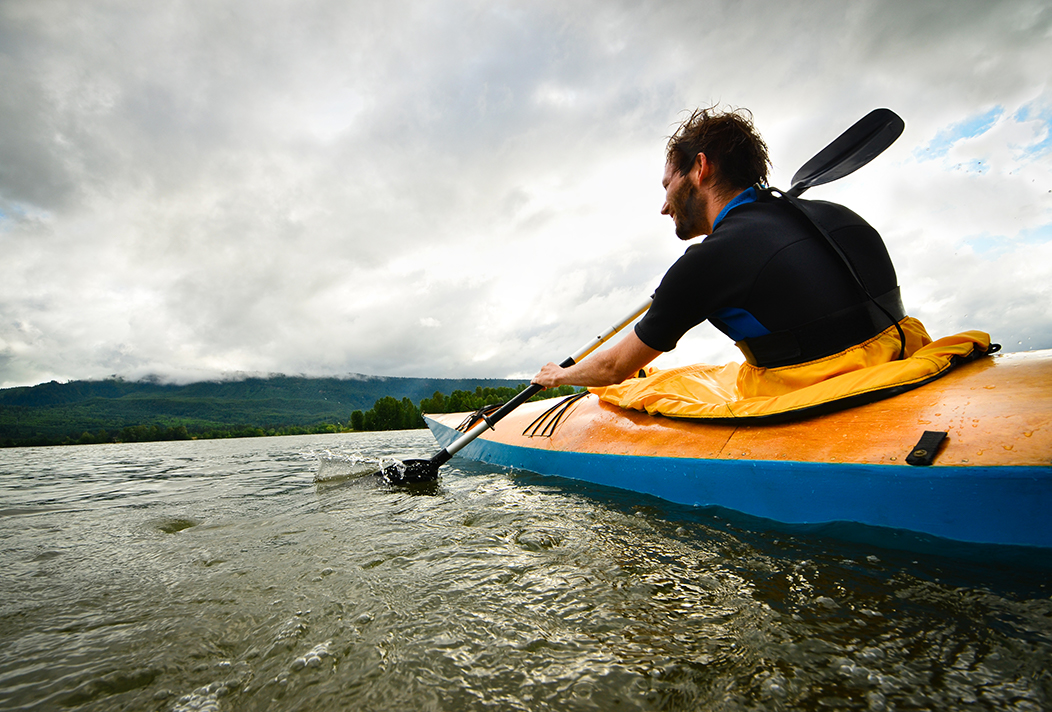 A man kayaks through calm waters