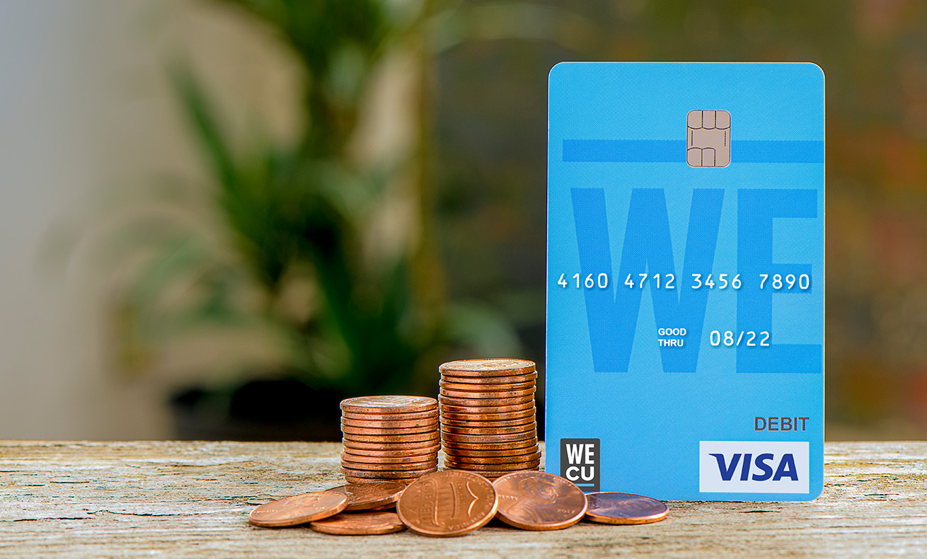 A stack of pennies next to the WECU debit card.
