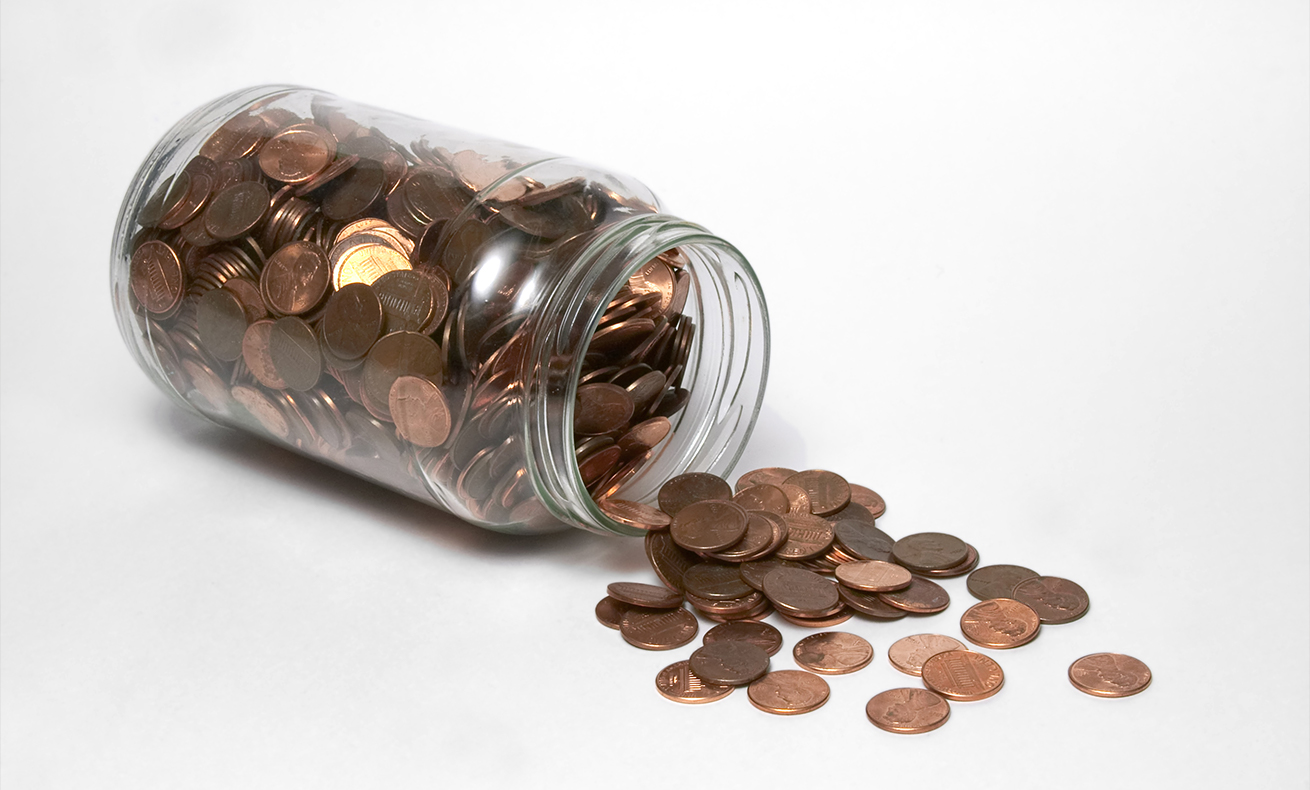 A jar of pennies on its side with pennies spilling out.