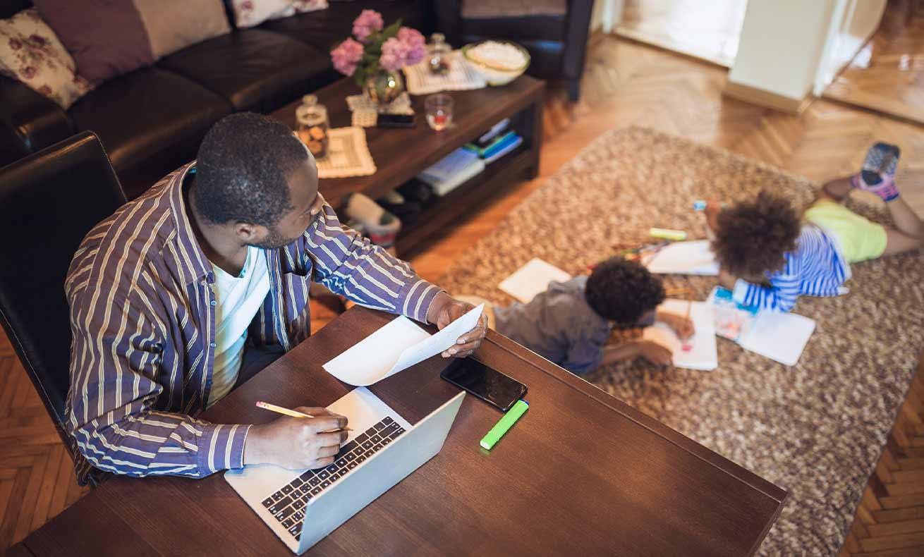 Father working from home while his two children are playing in the living room.