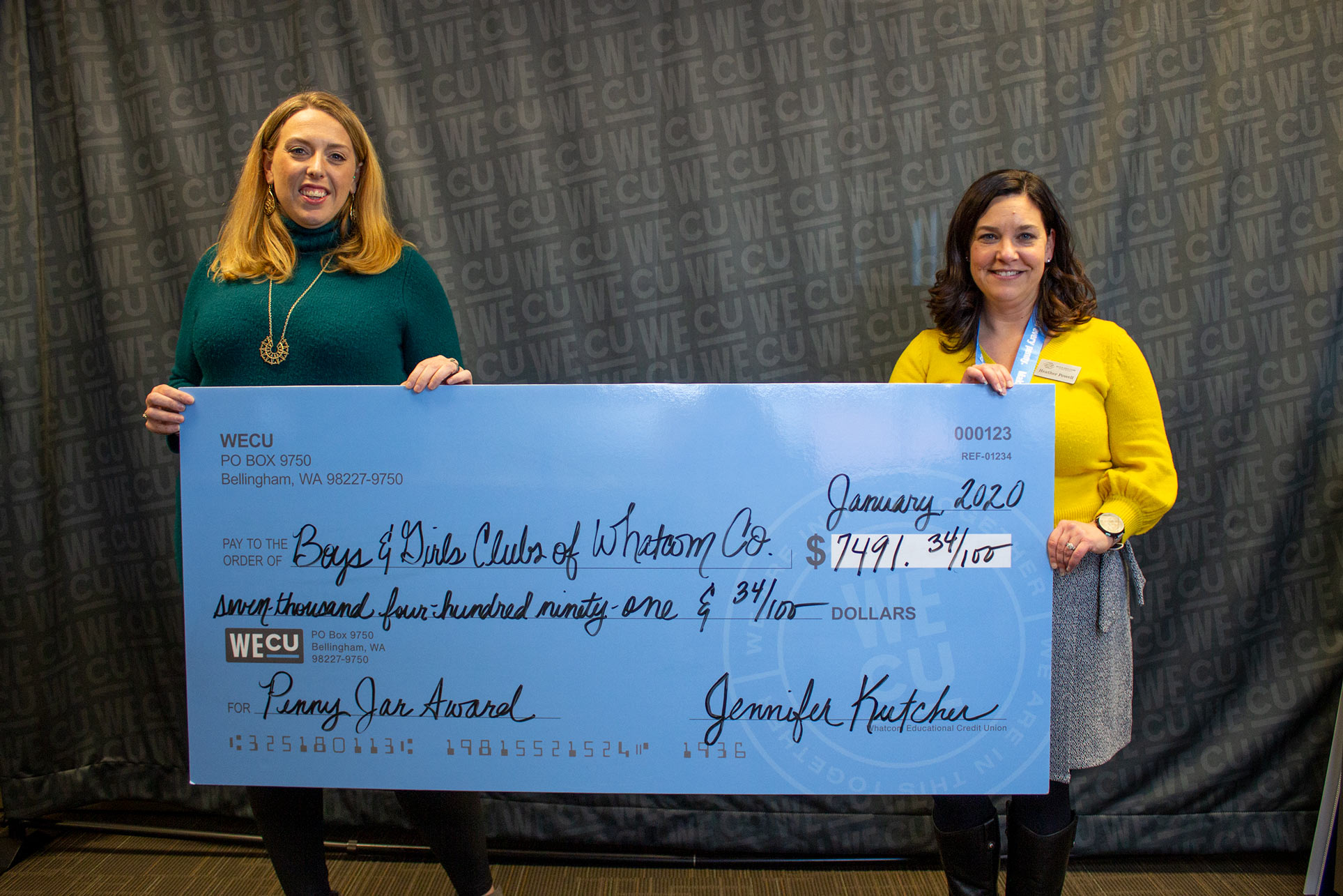 Heather Powell, CEO of Boys & Girls Clubs of Whatcom County, receives a check from WECU Community Impact Representative Virginia Gustke.