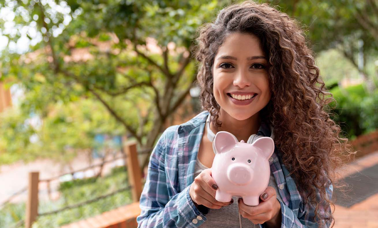 A young woman smiling and holding up a piggy bank.