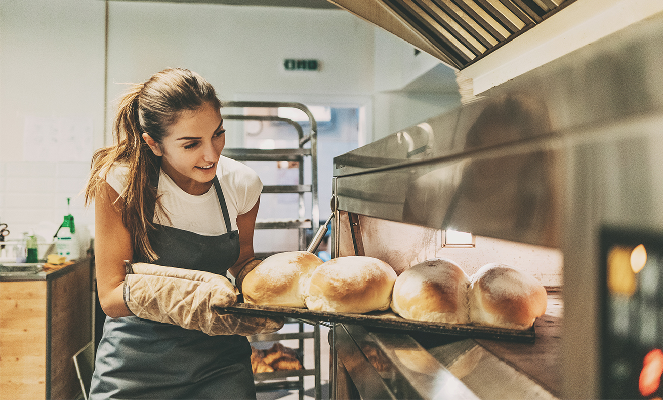 A baker pulls her fresh bread out of the oven.