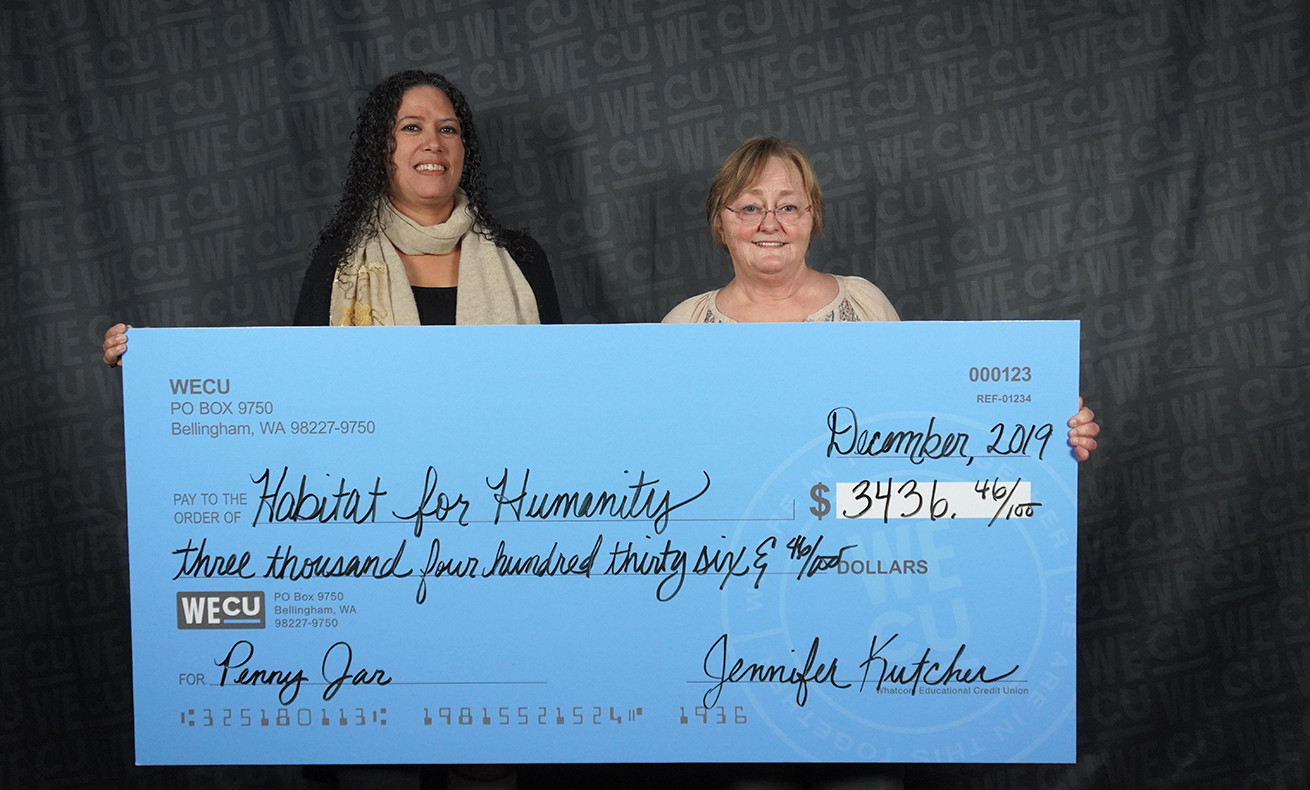Representatives from Habitat for Humanity pose for a photo with a check for $3,436.46.
