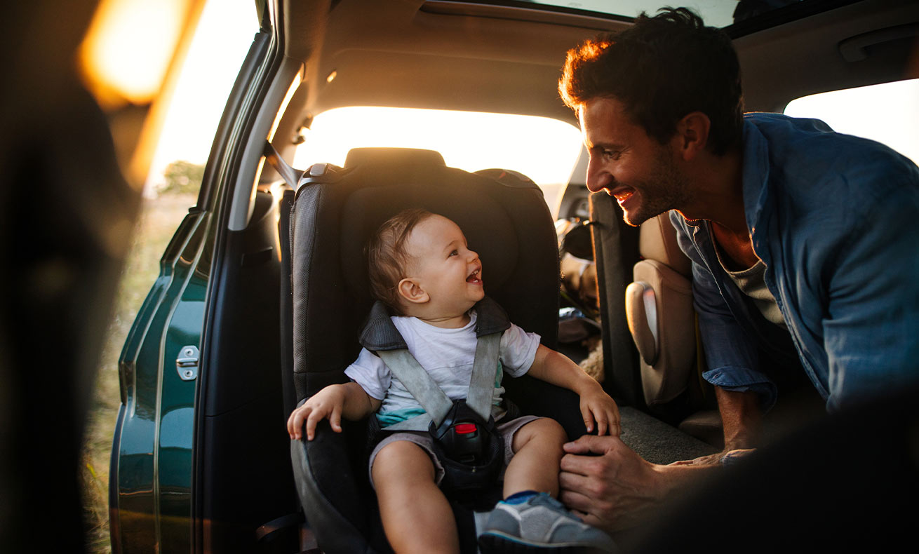 A man smiles at his child who is sitting in a car seat.