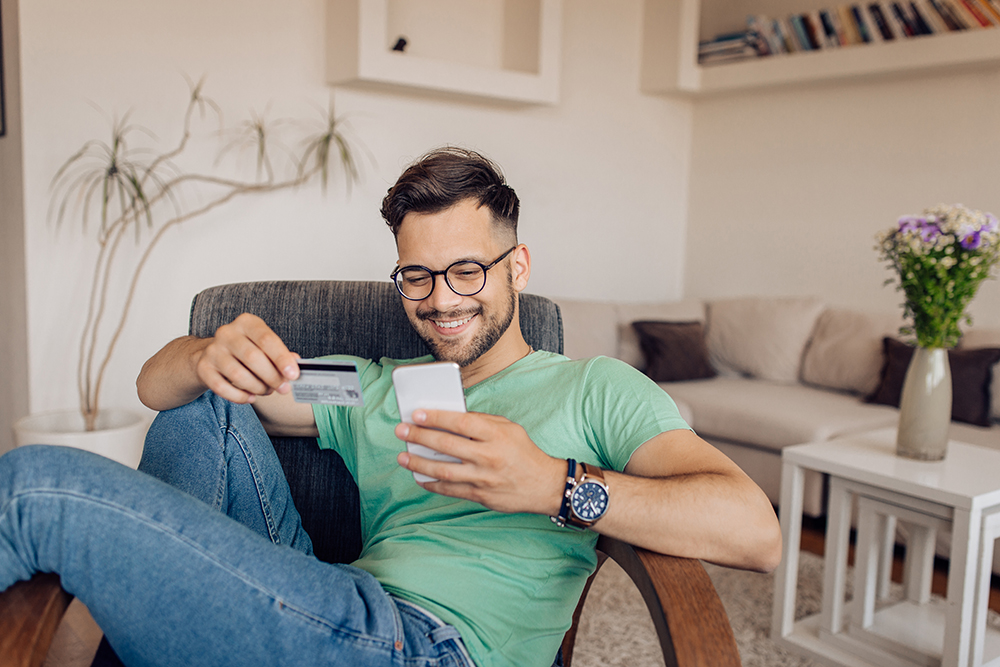 A man looks down at his credit card and phone, smiling.