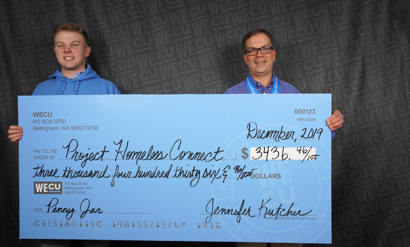 Representatives from Project Homeless Connect pose with a WECU employee for a photo with a check for $3,436.46.