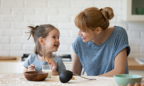 A woman has a conversation with her child at a table.