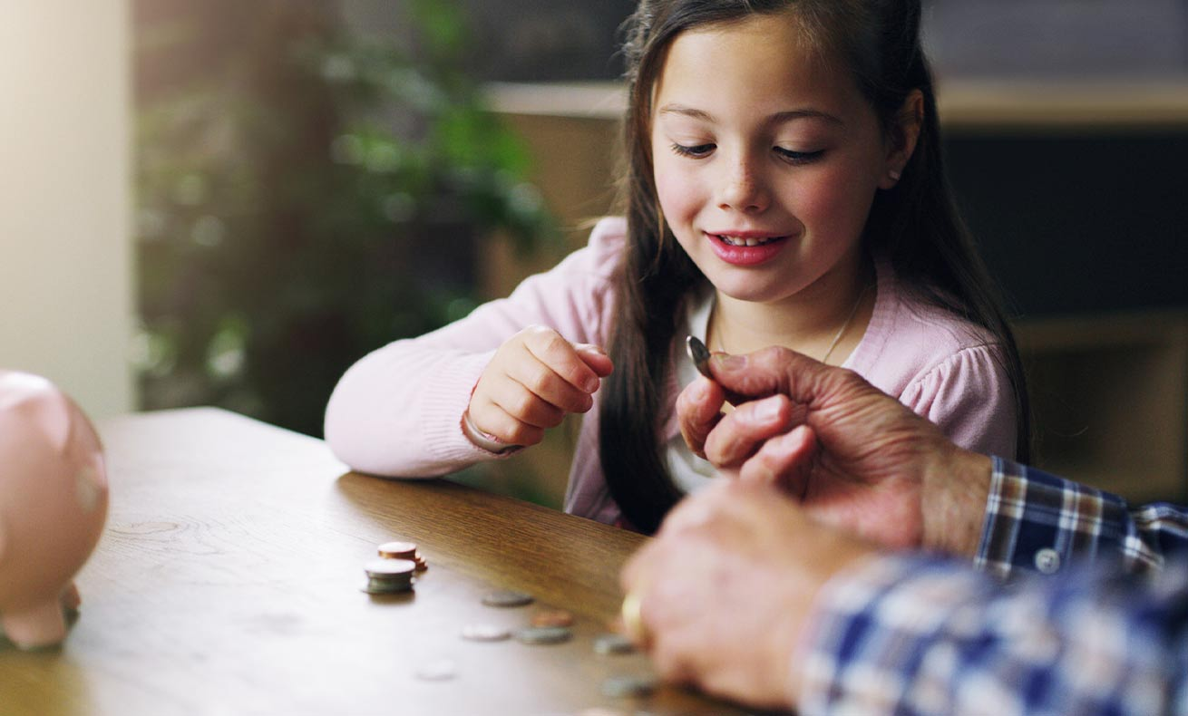 An elementary-age girl counts coins with her parents.