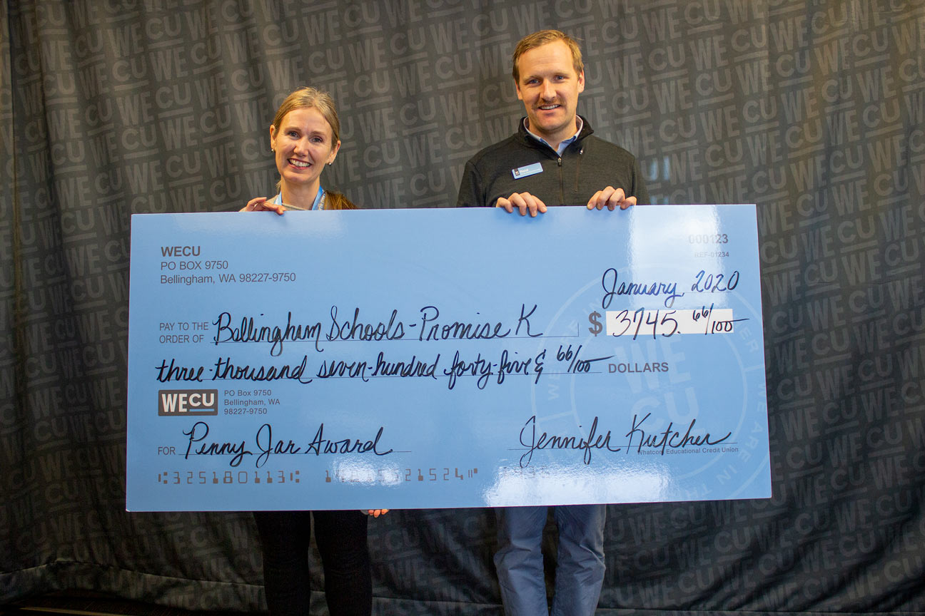 Kim Lund, Executive Director of Bellingham Public Schools Foundation, receives a check from WECU Director of Community Impact Reid Frederick.