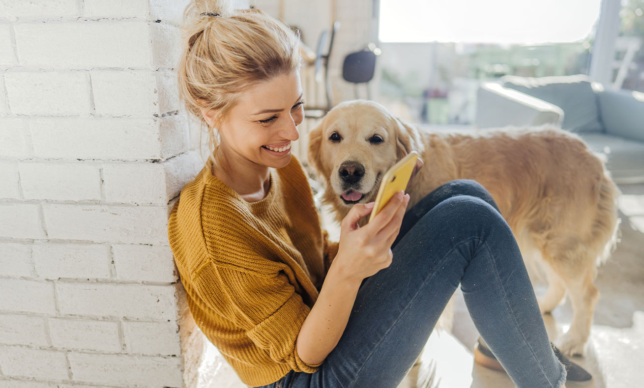 A young woman smiles and looks at her phone while a dog stands nearby.
