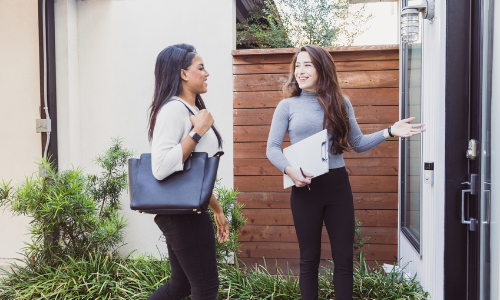 A woman with a clipboard addresses another woman carrying a leather bag outside a home.
