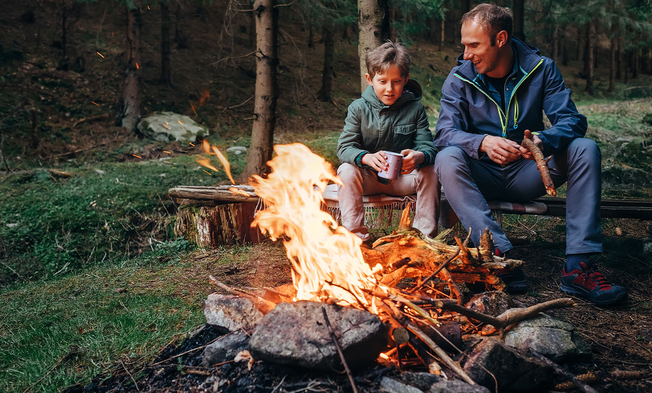 Father and son sit around a campfire.