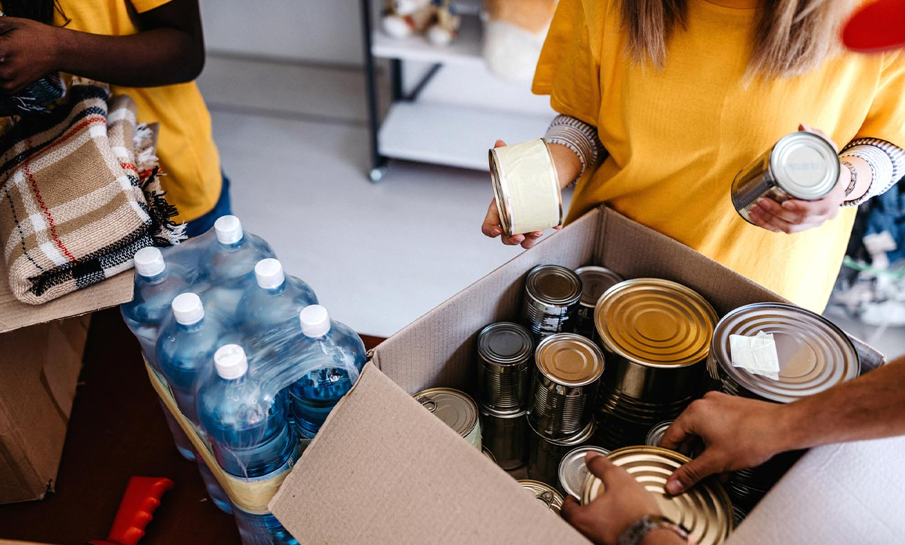 Volunteers stack cans and bottles of water in a box.
