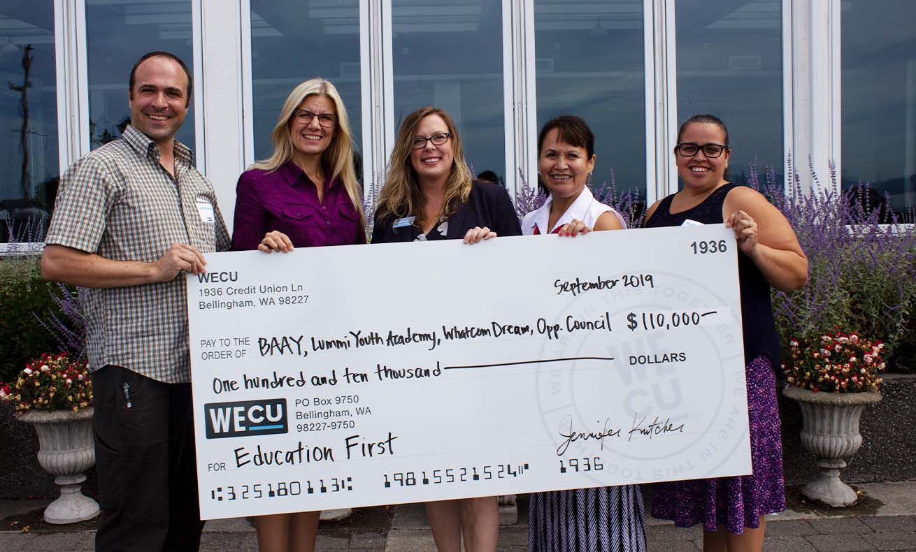 WECU CEO Jennifer Kutcher presenting a check for $110,000 to Bellingham Arts Academy for Youth, Lummi Youth Academy, Whatcom Dream, and Opportunity Council.