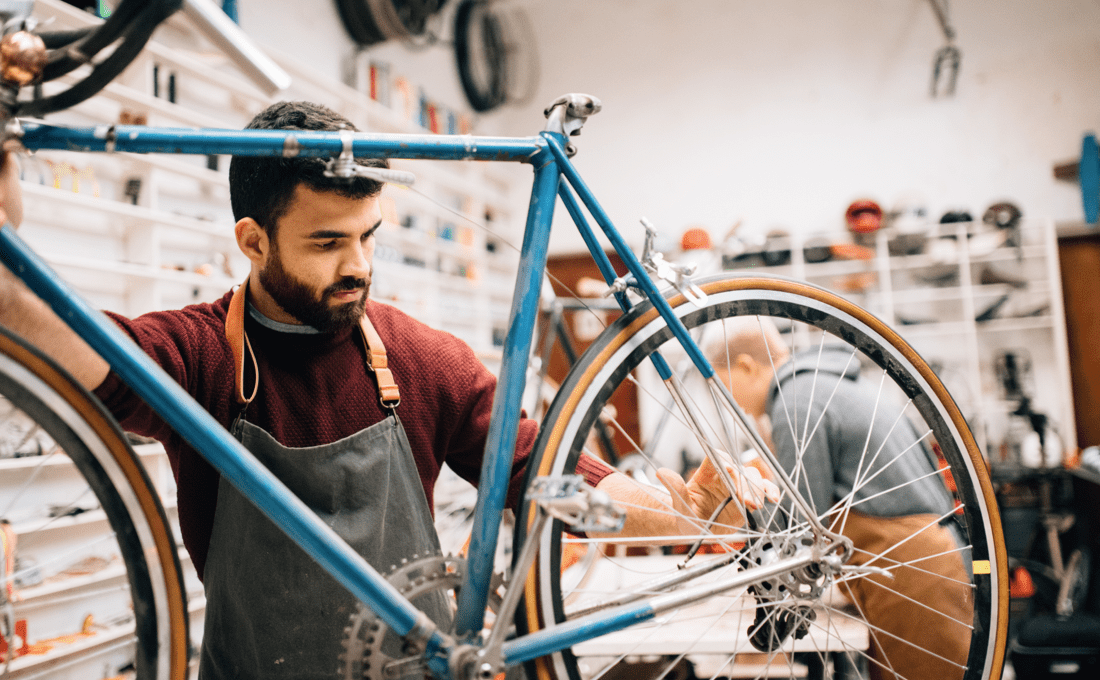 Photo of a man fixing a bicycle