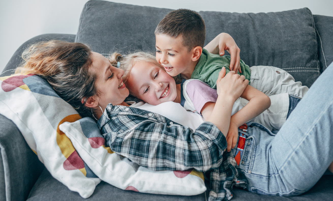 A mother lays on the couch with her two children in her arms.