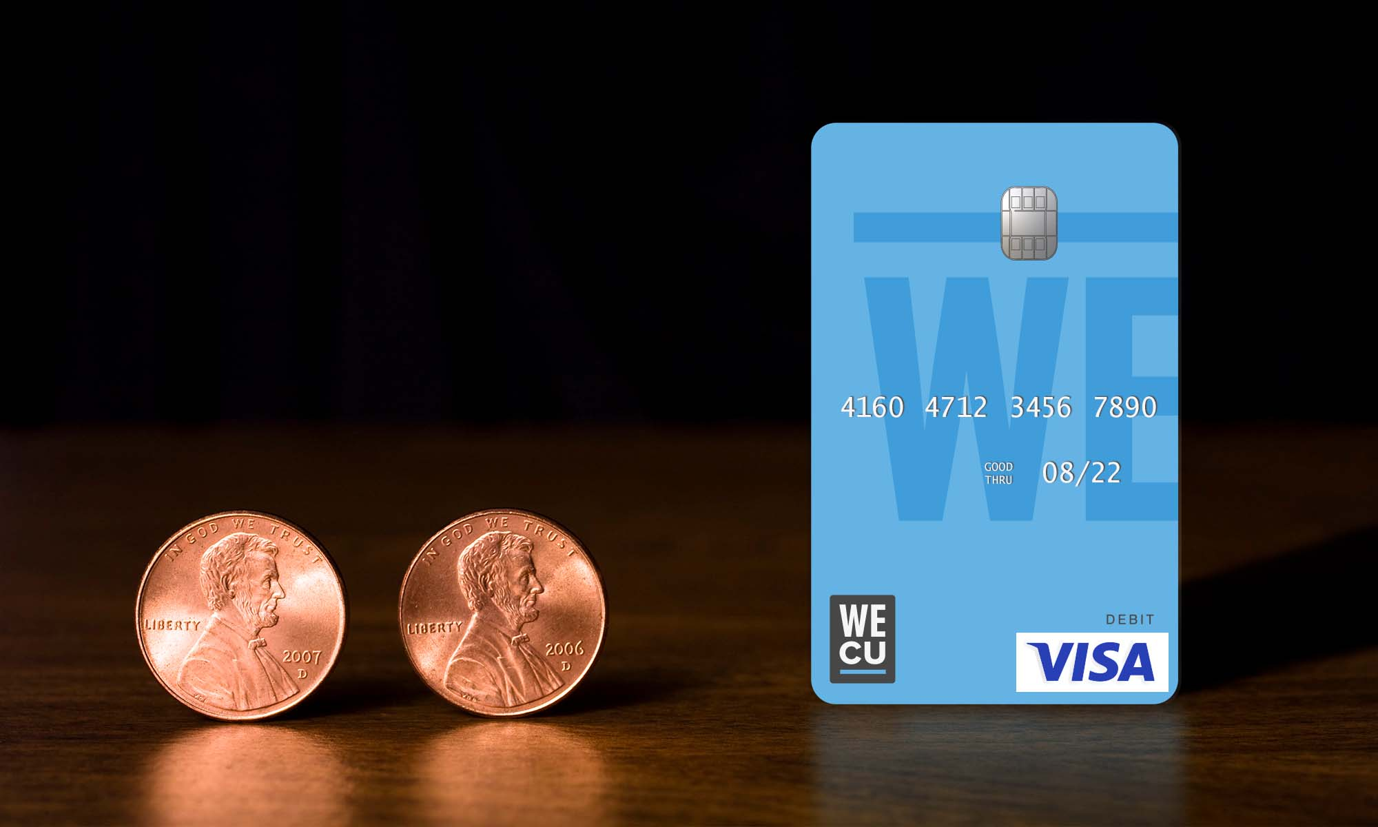 Two pennies next to the WECU debit card.