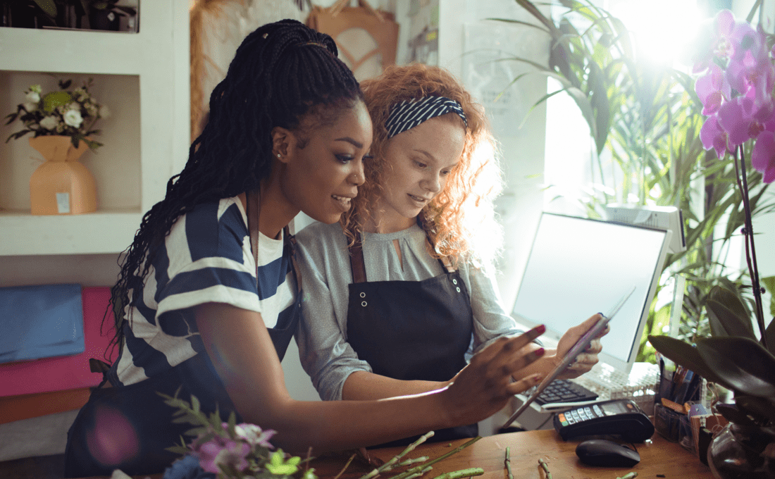Photo of two business women looking at a computer